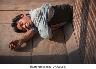 Bhaktapur District, Nepal, 13 Jun, 2017. Documentary. An identified of man lying on a sidewalk. Drunk guy sleeping on  the walkway.