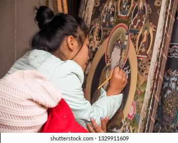 Bhaktapur - Nepal, 17 December 2018: Unidentified woman is painting a Thanka, Buddhist arts in Bhakpatur, Nepal.