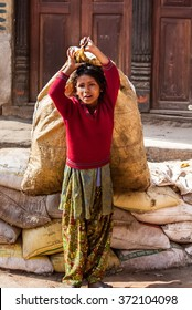 BHAKTAPUR, NEPAL - APRIL 19, 2013: Child Labour in Asia. Girl teenager drags the heavy bags on the square in Bhaktapur.