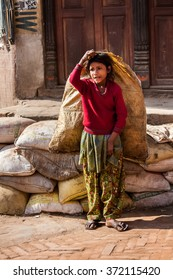 BHAKTAPUR, NEPAL - APRIL 19, 2013: Child Labour in Asia. Poorly dressed teen girl drags the heavy bags on the square in Bhaktapur.