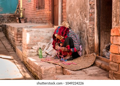 Bhaktapur, Nepal - December 16, 2017. Old woman  in Bhaktapur is siting in front of the house's door.