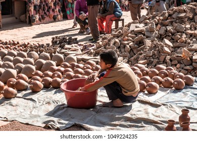 Bhaktapur, Nepal - December 16, 2017. An unknown Nepali boy in square of Bhaktapur is working with pottery.