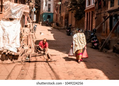 Bhaktapur, Nepal - December 16, 2017. People in square of Bhaktapur are working and walking on the village street.