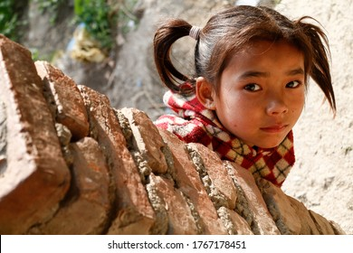 Bhaktapur Nepal - December 17 2019 - A shy little girl from Bhaktapur posing for a photo in Nepal.