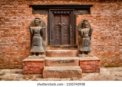 BHAKTAPUR, NEPAL - FEBRUARY 14, 2015: Two statues at the entrance to the Hindu temple of Taleju Chowk inside the Golden gate in Bhaktapur.
