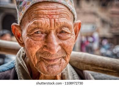 BHAKTAPUR, NEPAL – FEBRUARY 14,  2015: Portrait of an elderly man working as a porter in Bhaktapur, Nepal.