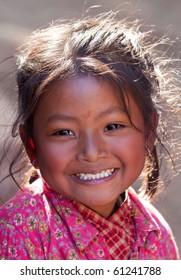 BHAKTAPUR, NEPAL - JANUARY 08: Portrait of smiling nevaris girl Lakshmi, 7 on the street of old town on January 08, 2010 in Bhaktapur, Kathmandu Valley, Nepal.
