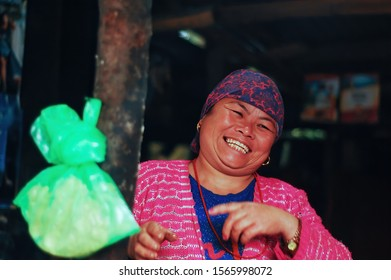 Bhaktapur / Nepal - October 2017: Middle aged, chubby, Nepali villager woman with scarf is laughing in order to bound with customers. Her laugh is fake. Sly, sneaky laughter. Golden earrings and watch