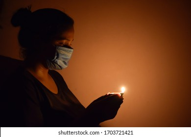 Bharuch, Gujarat / India - April 5 2020: Covid 19 Corona Virus, A girl in mask lighten up lamp and diya to show together we stand to fight Corona Virus. Selective focus on girl and black background.