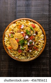 Bhel Puri is a savoury snack / Chaat item from India. It is made of puffed rice, vegetables and a tangy tamarind sauce. Popular roadside food. Served in a bowl over moody background. Selective focus