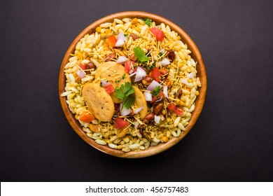 Bhel Puri is a savoury snack/Chaat item from India. It is made of puffed rice, vegetables & tangy tamarind sauce. Popular road side food. Served in bowl/ plate over moody background. Selective focus