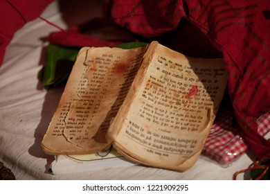 Bhilwara, India - April 26, 2016: old book containing mantras for a wedding ceremony with signs of intensive use is lying on the ground next to some pieces of cloth