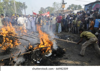 BHOPAL- DECEMBER 3: Violent victims hit the burning effigy during the rally to mark the 26th Year of the Bhopal Gas Tragedy in Bhopal - India on December 3, 2010.