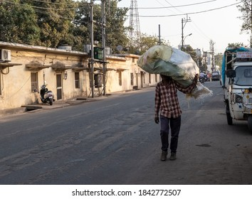 Bhopal, Madhya Pradesh, India - March 2019: An Indian labourer transporting a large sack of goods on his head while walking in the streets of the city.
