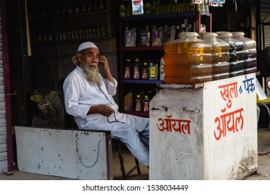 Bhopal, Madhya Pradesh/India - March 10 2019: A shopkeeper sits inside a shop that sells different kinds of motor oil in the old town.