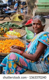 Bhubaneshwar, India – February 23, 2019: An old woman, wearing typical Indian clothes, sells flowers in the street