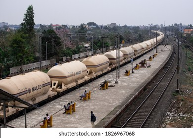 Bhubaneswar, India - February 4, 2020: A freight train pass through the city as people wait on benches at the station on February 4, 2020 in Bhubaneswar, India