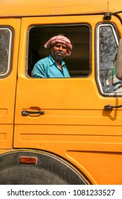 Bhubaneswar, Odisha, India - January 8, 2014 - Portrait of a indian truck driver with yellow truck at Odisha.
