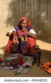 BHUJ, RAN OF KUCH, INDIA - JANUARY 14: The tribal woman in the traditional dress selling souvenirs in the ethnic village on the desert in the Gujarat state in India, Ran of Kuch in January 14, 2015