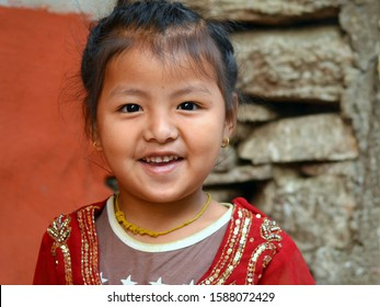 BHULBHULE, ANNAPURNA CIRCUIT / NEPAL - APRIL 11, 2016: Little Nepali Gurung girl smiles for the camera, on April 11, 2016.