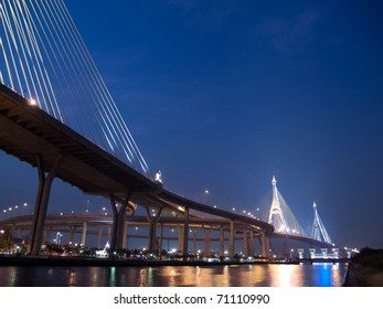 Bhumibol Bridge also casually call as Industrial Ring Road Bridge with floodgate illuminate with spotlight at night scene, Samut Prakarn, Thailand