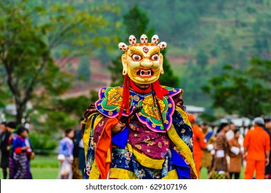 Bhutan, masked dancer at a traditional monastery festival the Wangdue Phodrang Tsechu. A monk in a colorful dress with mask during the tsechu (dance festival) in Wangdue, Bhutan.