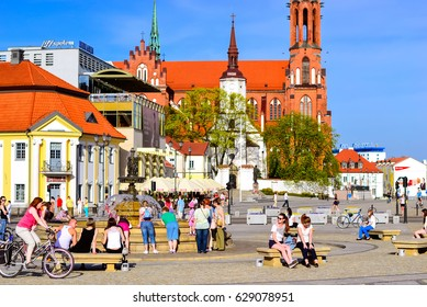 Bialystok, Poland - April 29, 2012: Tourists walk in sunny summer day on pavers central square of Kosciusko Market. On background Cathedral Basilica of Assumption of Blessed Virgin Mary in Bialystok