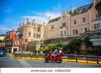 BIARRITZ, FRANCE - July 2018: Couple on the motorcycle on the street of historical Biarritz center, France