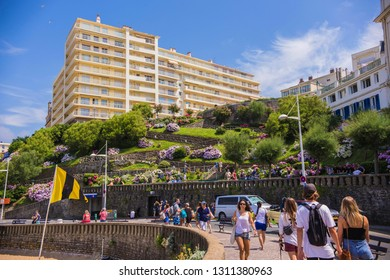 BIARRITZ, FRANCE - June 2018: People by the sea coast at Biarritz, France. Crowded beach at Biarritz, Atlantic Ocean coast in France