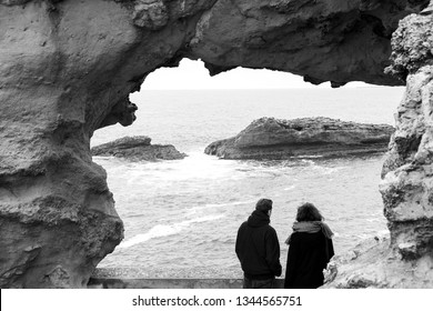 Biarritz, France. Unrecognizable couple (back view) admiring seascape with  rocks at Rock of the Virgin Mary site, iconic Biarritz landmark. Cloudy spring day at Atlantic Ocean. Black white photo.