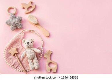 Bib and wooden toys. Set of baby stuff and accessories for girl on pastel pink background. Baby shower concept. Fashion newborn. Flat lay, top view