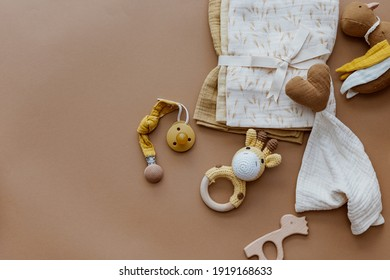 Bib and wooden toys. Set of baby stuff and accessories for newborn on brown background. Baby shower or baby care  concept. Fashion newborn. Flat lay, top view