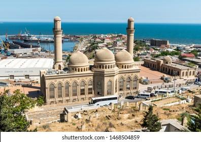 Bibi-Heybat, Baku, Azerbaijan - May 12, 2019. View over Bibi-Heybat mosque in Baku, with shipyard facilities, Caspian Sea and Bibi-Heybat settlement in the background.
