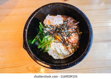Bibimbap is rice topped with namul(seasoned vegetables) and meat, and gochujang or other sauce. The toppings are usually stirred together with the rice before eating.