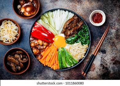 Bibimbap, traditional Korean dish, rice with vegetables and beef. Top view, overhead, flat lay