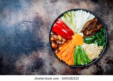 Bibimbap, traditional Korean dish, rice with vegetables and beef. Top view, overhead, flat lay, copy space