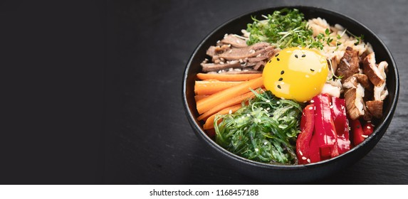 Bibimbap - traditional Korean dish with rice, vegetables, beef. Panorama with copy space