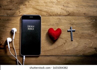 Bible app in smart phones with red heart and silver cross on wooden table, read and listen to the voice of God, symbol of christian concept.