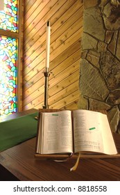 A bible and a candle in a candlestick inside a church.
