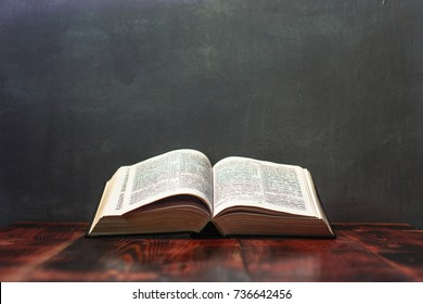 Bible and candle on a red wooden table. Beautiful background.Religion concept