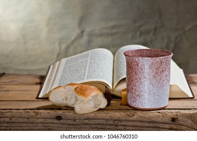Bible, Chalice And Bread on the Wooden Desk.