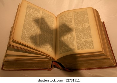 Bible with cross shadow on a shroud