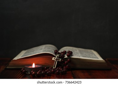 Bible crucifix and beads with a candle on a red wooden table. Beautiful background.Religion concept.