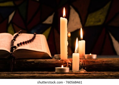 Bible crucifix and beads with a candle on a old oak wooden table.  Beautiful Stained-glass windows background.Religion concept.