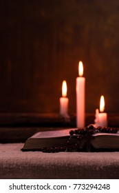 Bible crucifix and beads with a candle on a old oak wooden table.  Beautiful gold background.Religion concept.