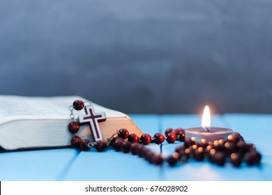 Bible and the crucifix on a blue wooden table. Beautiful background.Religion concept