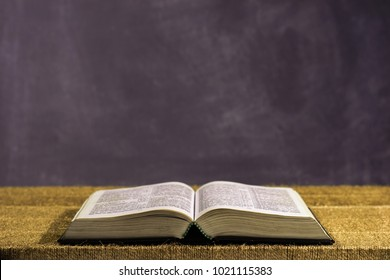 Bible and the crucifix on a gold table. Beautiful dark background.Religion concept.