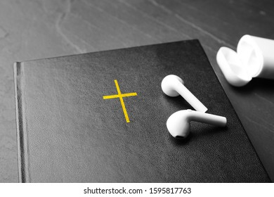Bible and earphones on black table, closeup. Religious audiobook