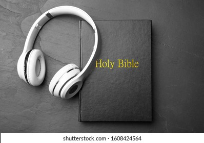 Bible and headphones on black background, top view. Religious audiobook