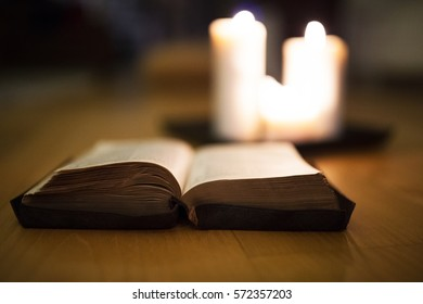 Bible laid on wooden floor, burning candles in the background